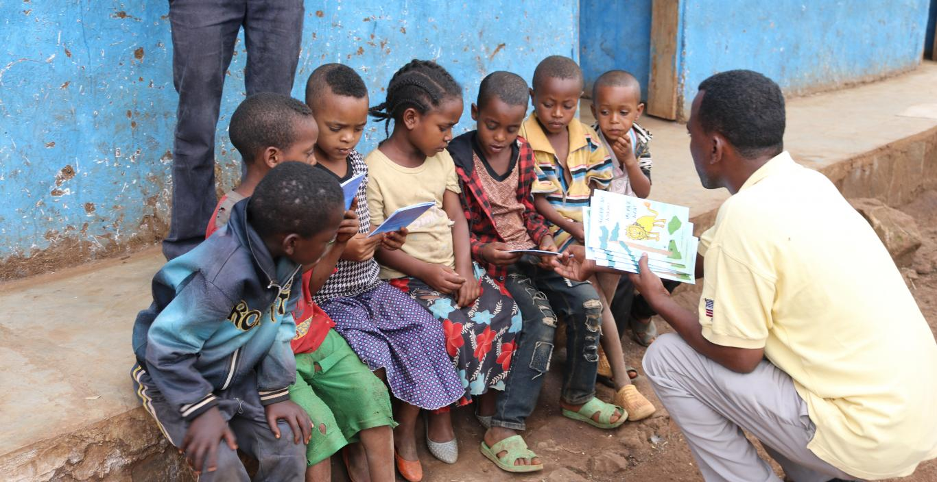 Children in Ethiopia sitting on the sidewalk while their teacher shows them a book.