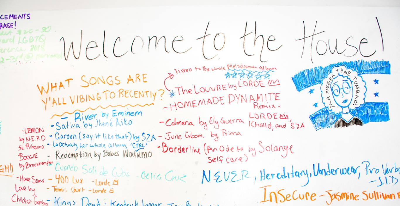 "White board covered in song titles, says ""Welcome to the House"" at the top."