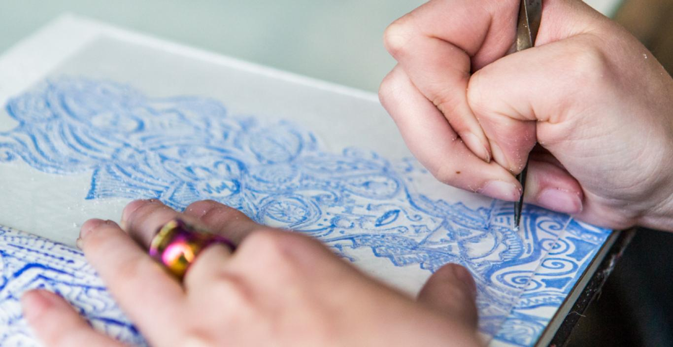 Hands etching a blue design