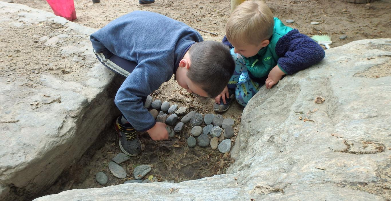 Two small children exploring rocks and sand