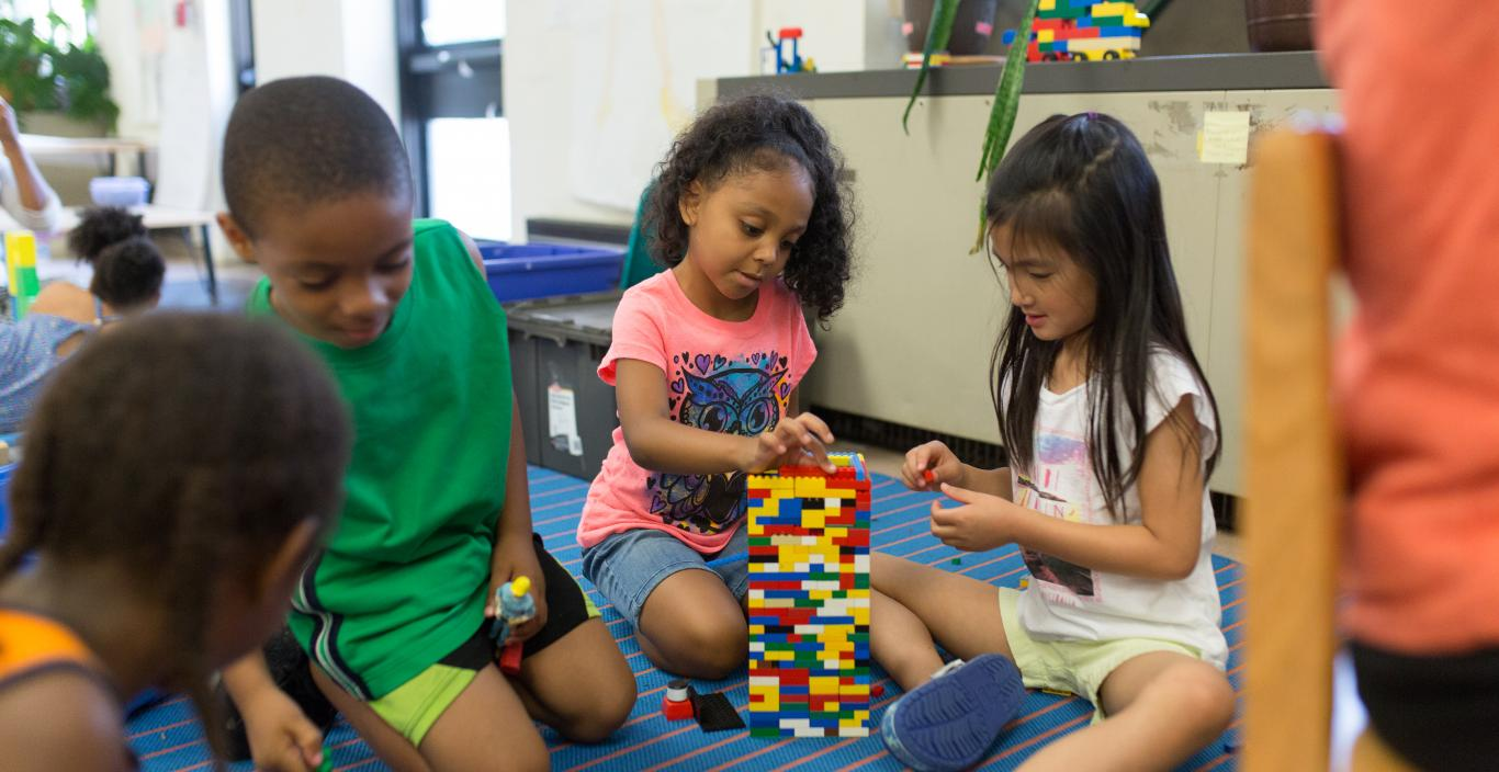 Group of children helping each other build a structure with colored blocks