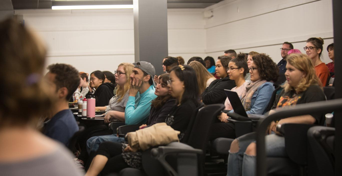 students listen to a presentation in screening room