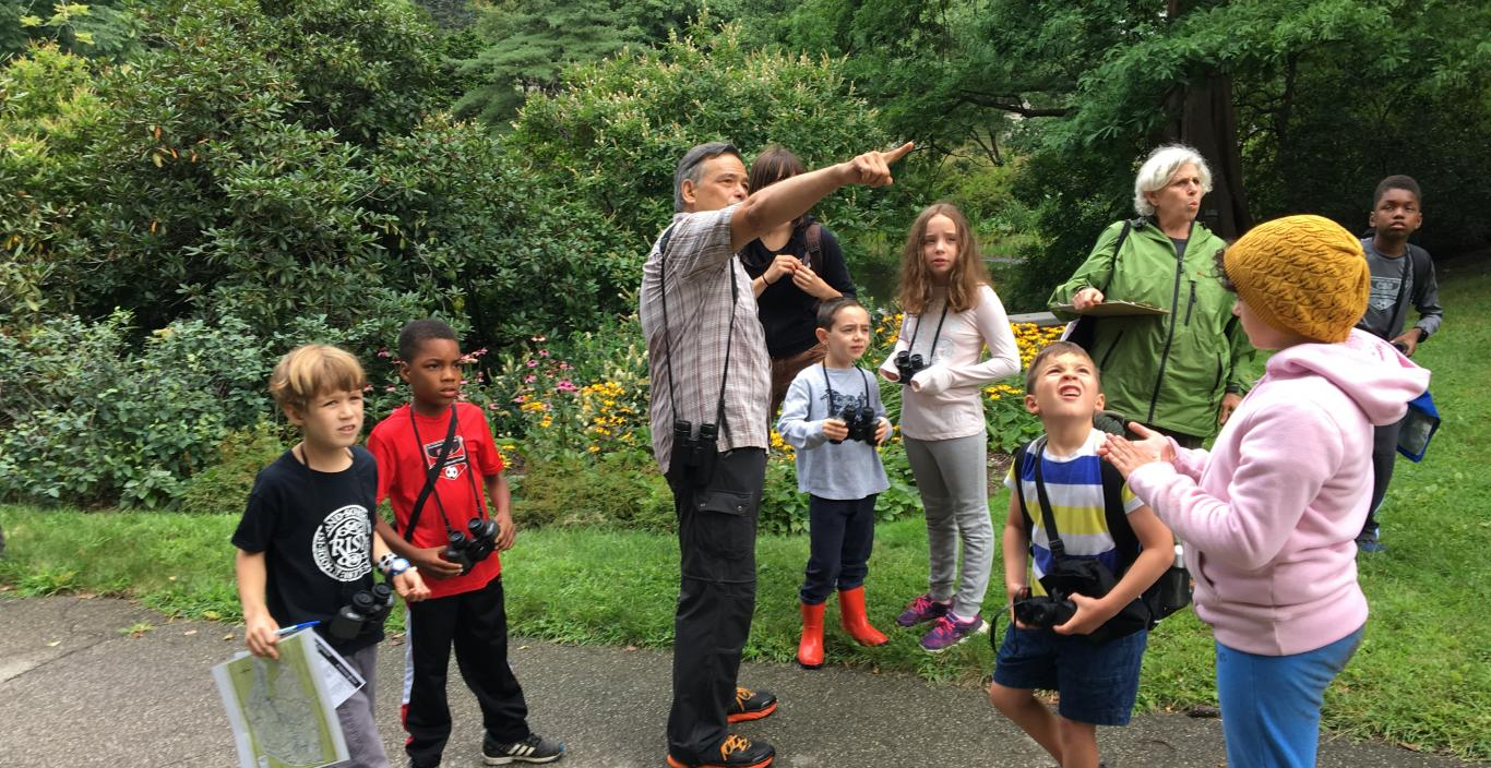 Mt Auburn Morimoto Rauchwerk students exploring outdoors with cameras. Group leader is pointing at something and everyone is looking