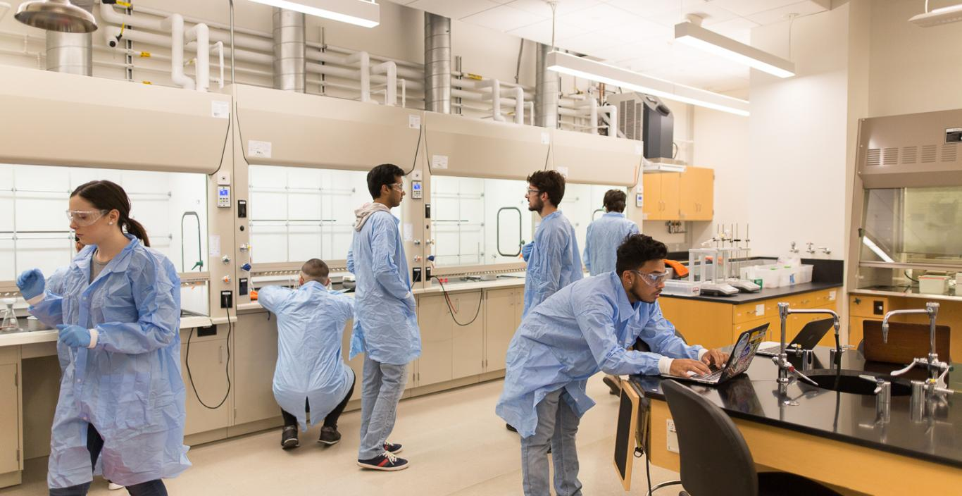 Landscape view of the lab with students working in their lab coats.