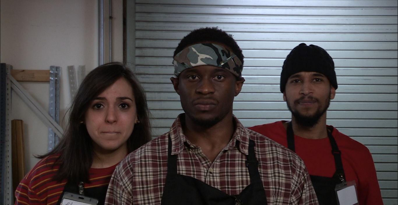 Three people wearing black aprons look into the camera