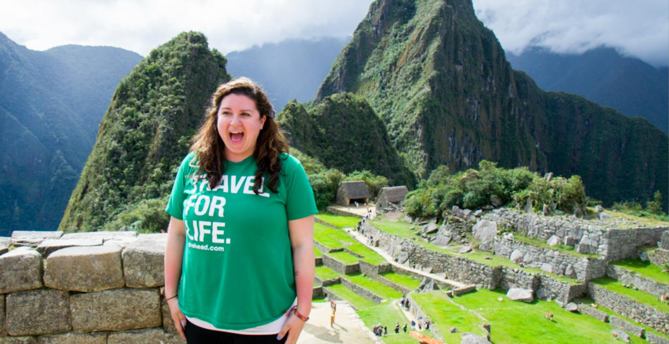"girl wearing shirt that says ""travel for life"" in front of mountains and stone structures with her mouth open with excitement"
