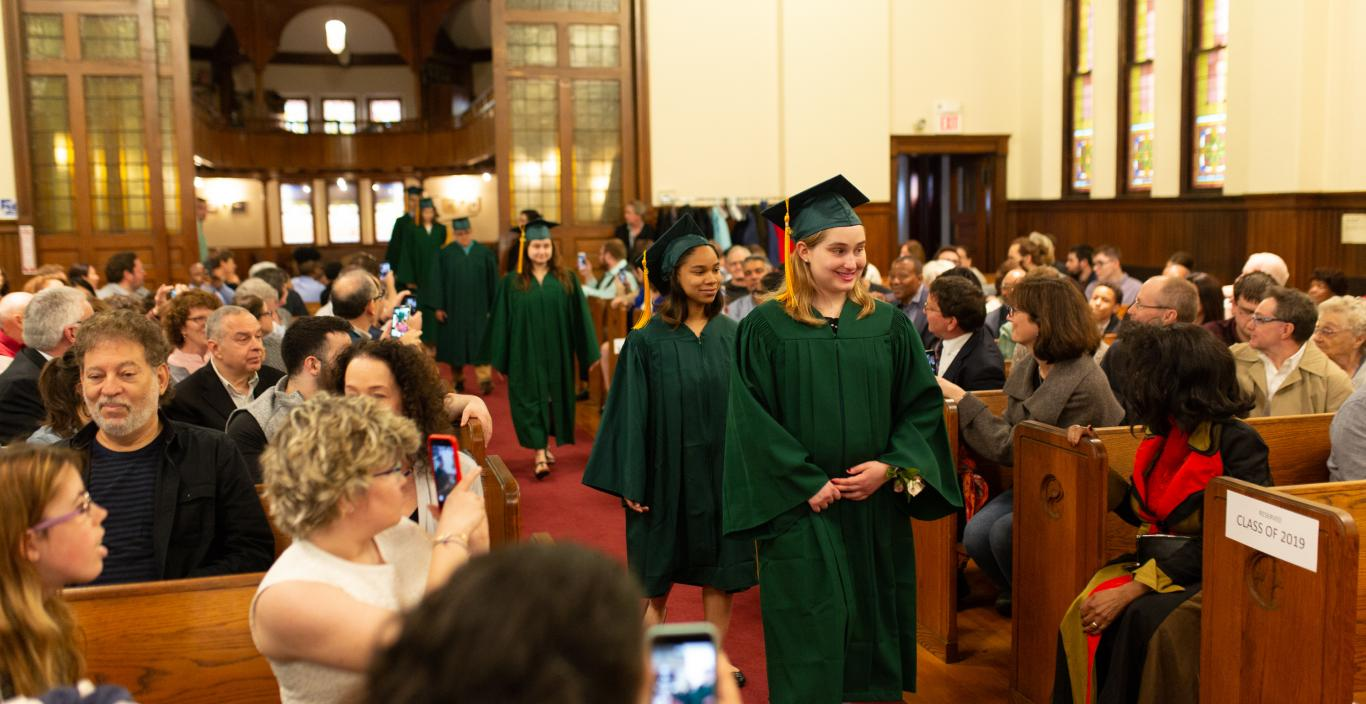 Students in cap and gown proceed into the church.