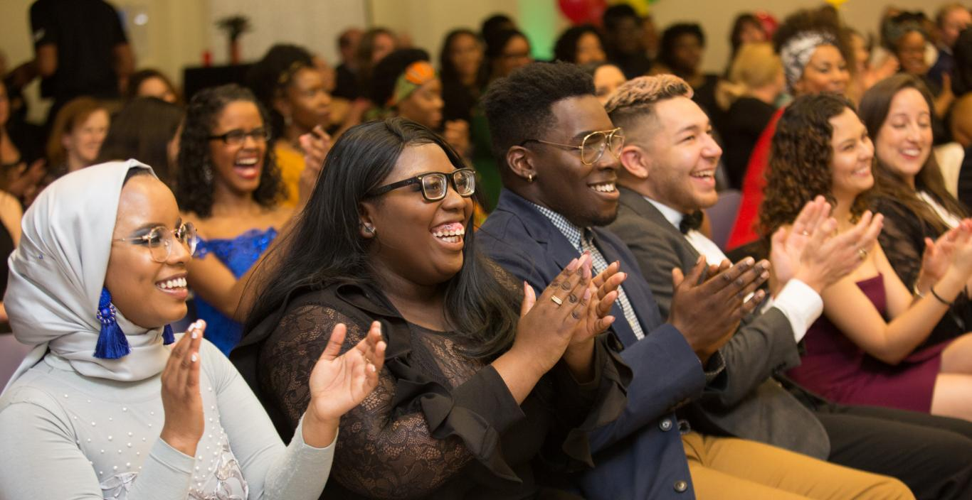 Students in an audience dressed up for the Unity Gala, applauding the award winners.