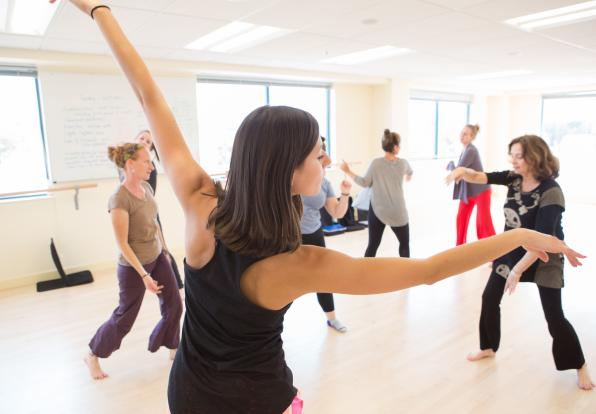 Students dance in a brightly lit studio.