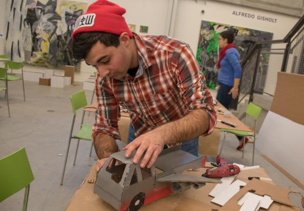 A student works on a gray pickup truck made of cardboardin the bottom level of Lunder Arts Center.
