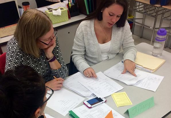Teachers working on math problems together around a table