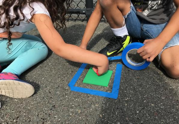 Children on sidewalk using colored tape to make shapes