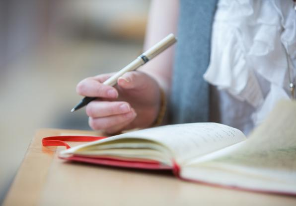 closeup of woman writing in notebook