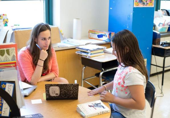 Middle school student and teacher at desk reading