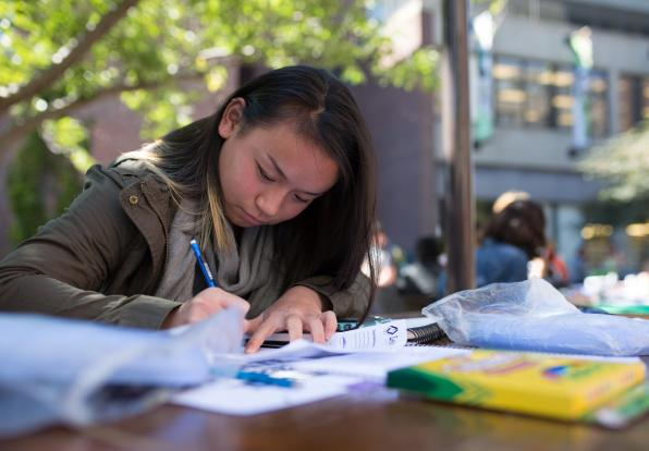 female student filling out a form on a table outside
